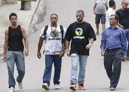José Júnior, de camisa preta do AfroReggae e mais atrás de camiseta preta com a mão na cabeça, o irmão de Marcinho VP, que não queria aparecer, no dia da ocupação do Complexo do Alemão