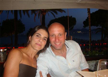 Sérgio Côrtes tendo ao fundo o Mar Mediterrâneo posa com a esposa num restaurante de Monte Carlo com a carta de vinhos na mão