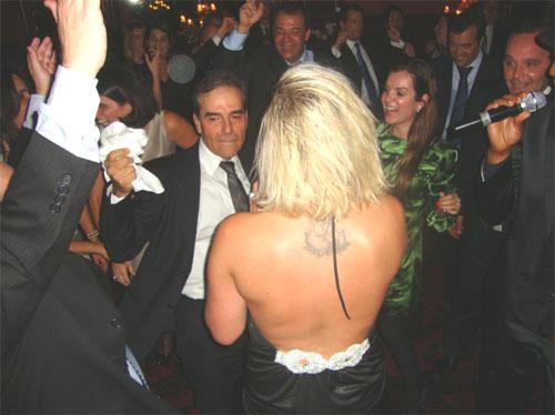 """Sérgio Dias, de guardanapo na mão, dança na rodinha com loura tatuada, no Hotel Ritz, em Paris. Cabral ao fundo vibra com o """"show"""""""