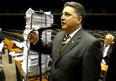 Garotinho com a pilha de documentos e o deputado Miro Teixeira logo atrás