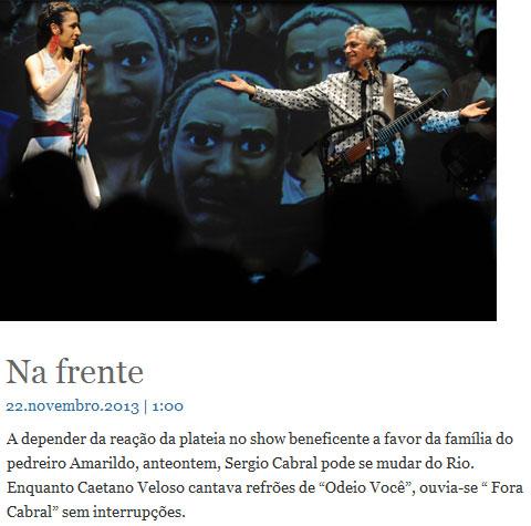 Marisa Monte e Caetano Veloso cantam com máscara de Amarildo ao fundo; abaixo nota da colunista Sonia Racy, do Estadão