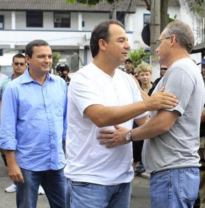 Cabral e Beltrame se abraçam sob o olhar sorridente de Regis Fichtner
