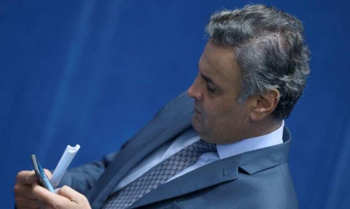 Aécio Neves, na sessão de ontem do Senado, confere no celular a notícia da delação de Joesley Batista