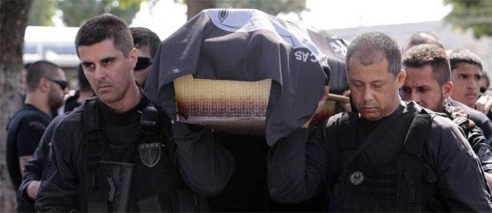 Colegas da Core carregam o caixão de policial assassinado no Jacarezinho