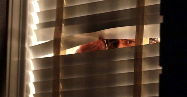 Aécio Neves espreita pela janela de casa enquanto Senado decidia